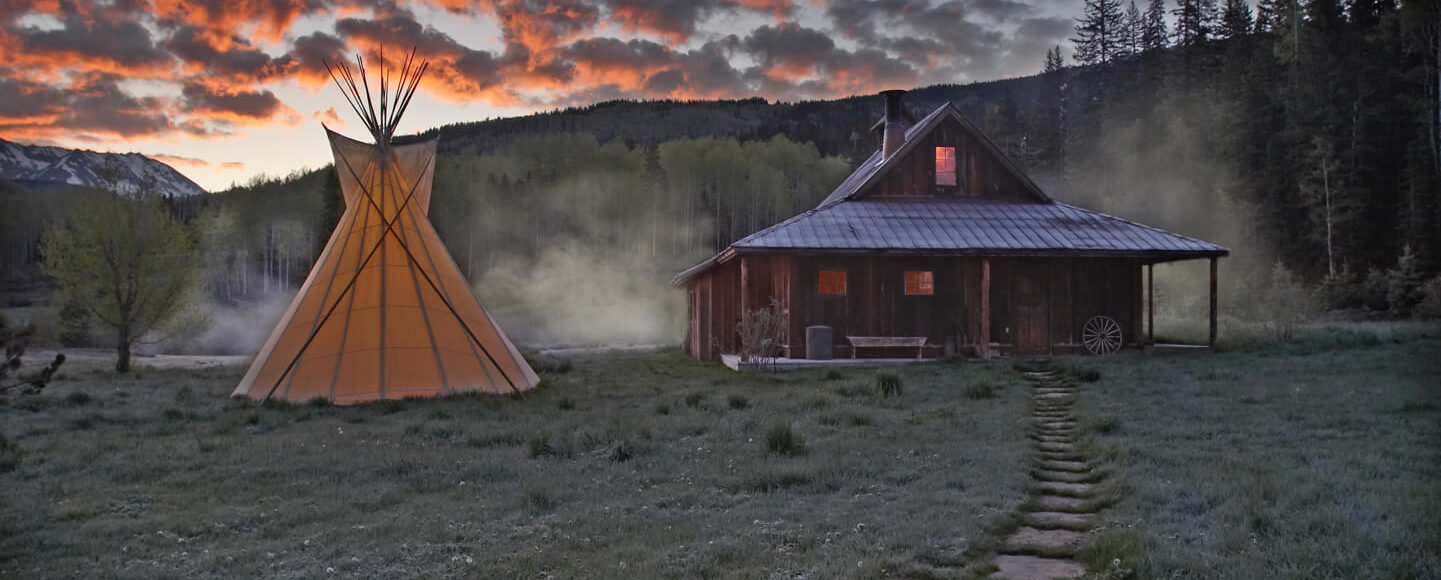 Tipi and bathhouse cabin at dawn
