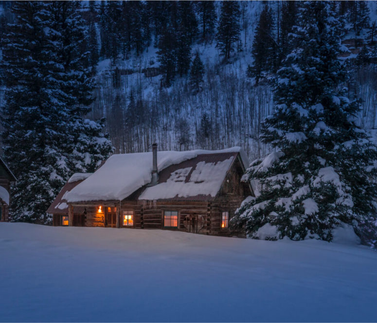 Snowy cabin at dusk