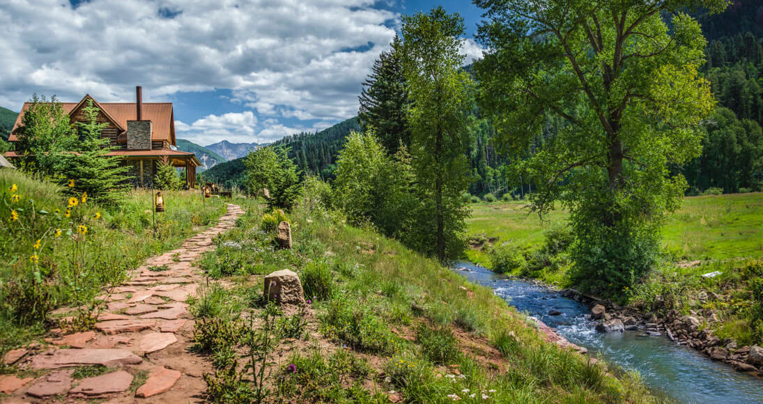 Cabin in front of river and Colorado mountain landscape